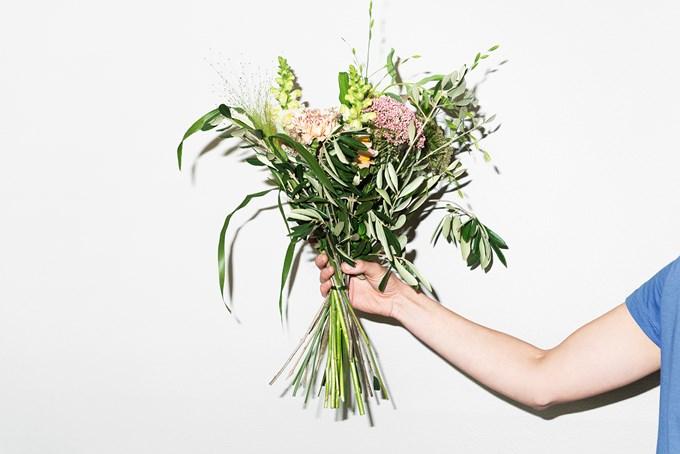 Arm som holder grønn blomsterbukett mot hvit vegg. Bilde