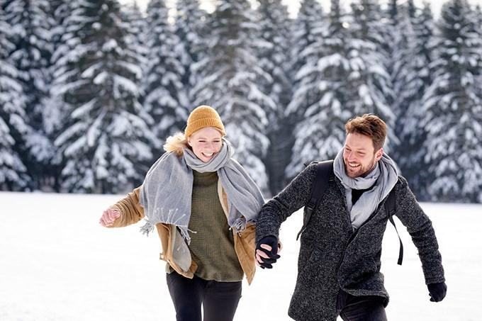 Mann og dame løper i vinterlandskap. Bilde