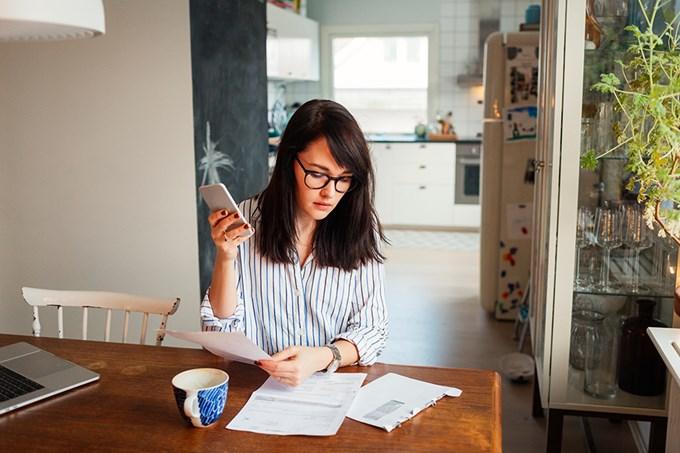 Kvinne sitter ved et bord og betaler en regning. Foto.