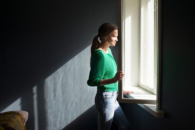 Kvinne ser ut av et åpent vindu. Foto.