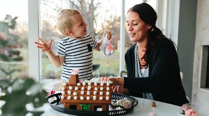 Kvinne og barn pynter pepperkakehus. Foto.