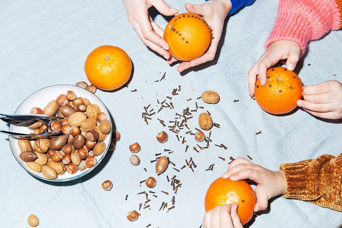 Skål med nøtter og nøtteknekker, hender som holder i appelsiner med nellikspiker   foto