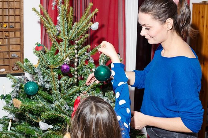 Kvinne og barn pynter juletre. Foto.
