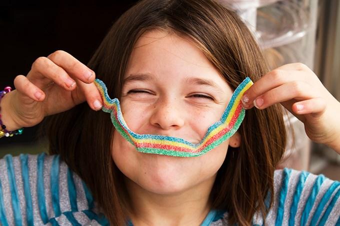 Smilende jente med snopesnor i forskjellige farger foran munnen | foto