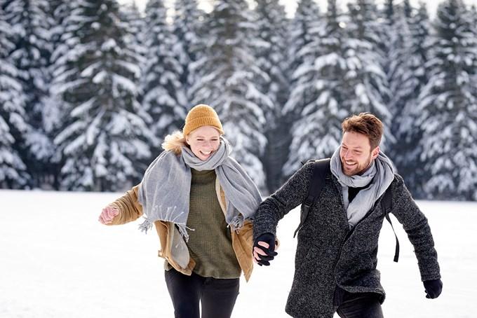Mann og dame løper i snøen. Bilde