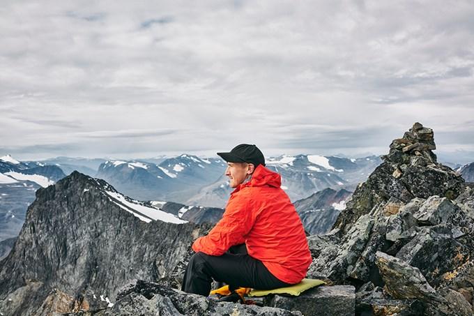 Bilde av mann som sitter på fjelltopp og stirrer utover landskapet.