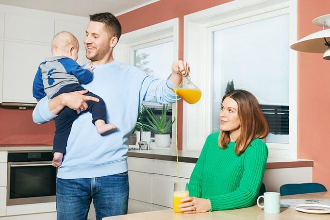 En mann heller juice i glasset til en kvinne, samtidig som han holder et barn. Foto.
