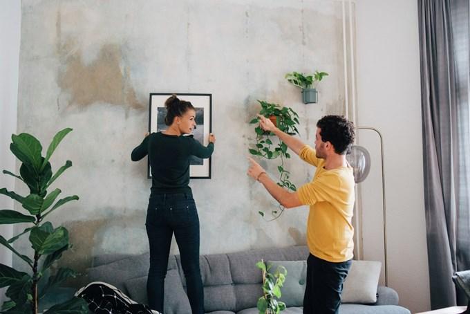 Mann og dame henger opp bilde på veggen. Foto