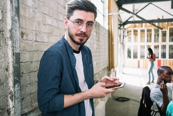 Mann med smarttelefon. Foto