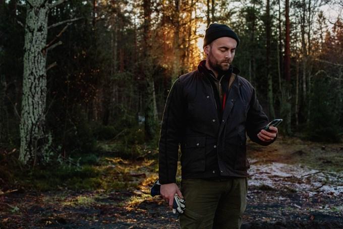 Mann i skogen med smarttelefon. Foto