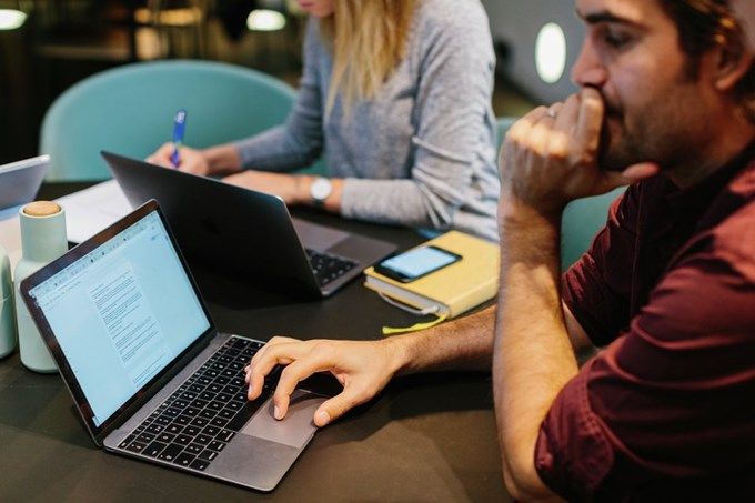 Kollegaer sitter med laptoper. Foto