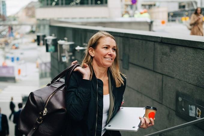 Forretningskvinne bærer laptop. Foto