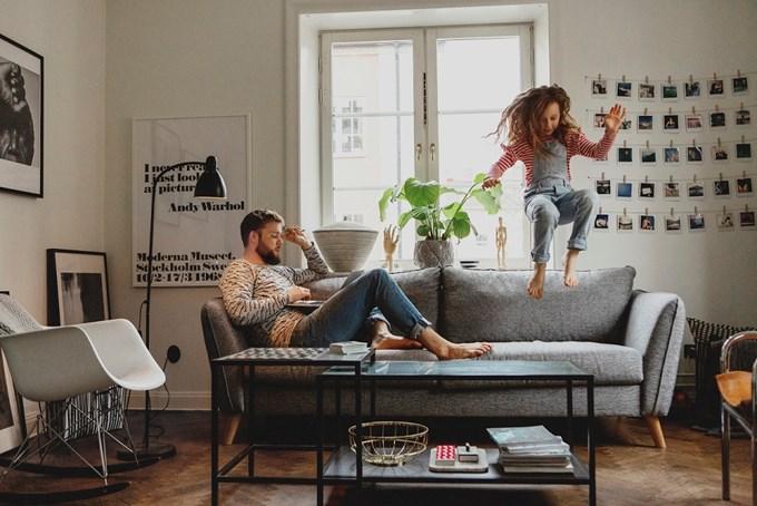 Mann med laptop, jente som hopper i sofaen | foto