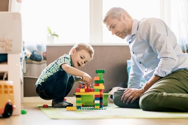 Far og sønn bygger lego. Foto.