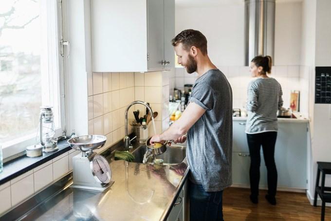Par på kjøkkenet med oppvask og matlaging | foto