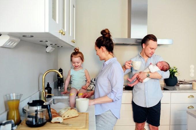 Familie på kjøkken, mor og far og to små barn | foto