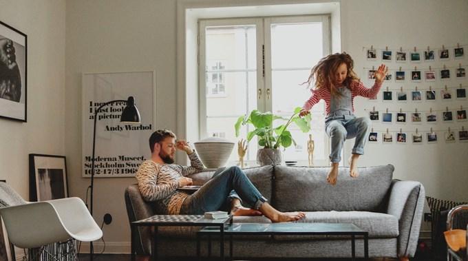 Pappa på laptop og jente som hopper i sofaen. Foto