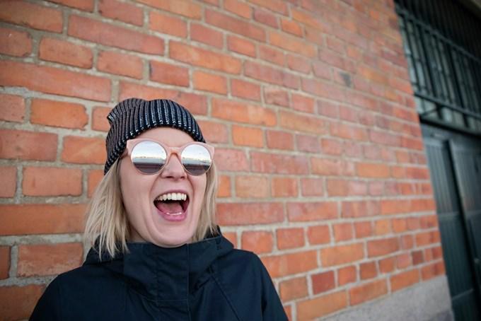 Dame med solbriller og stort smil. Bilde