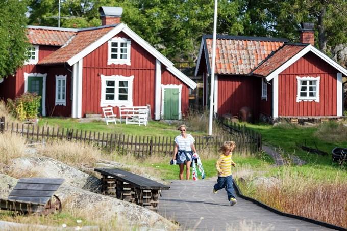 Mor og sønn foran en hytte. Foto