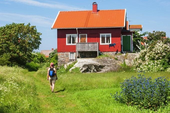 Dame går mot en rød hytte en solfylt sommersdag. Foto
