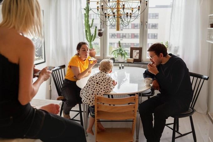 Familie sitter ved kjøkkenbordet og spiser. Foto