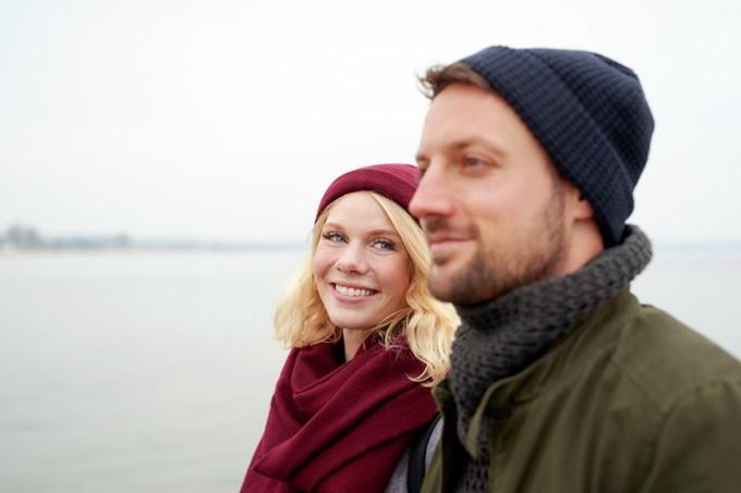 Mann og dame går langs sjøen. Foto