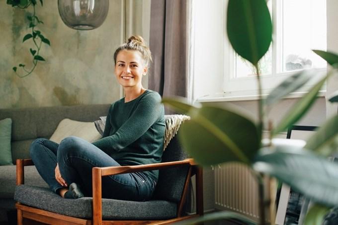 Ung kvinne sitter i en lenestol og smiler. Foto