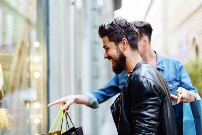 To menn med handleposer kikker inn butikkvindu og ler. Foto