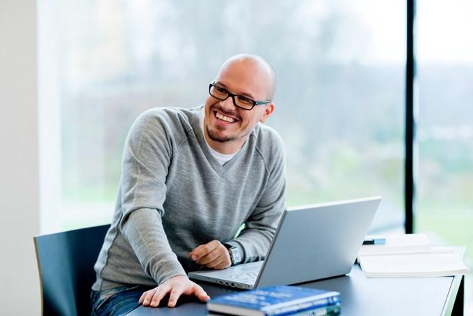 Mann som ler og sitter foran en PC | Foto.