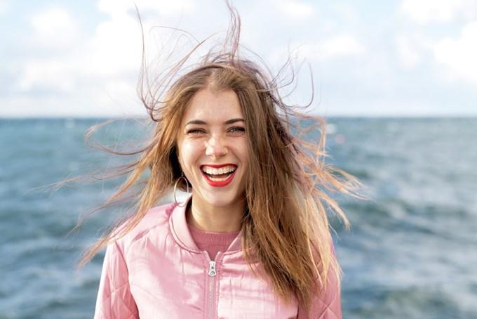 Dame med vind i håret foran sjø | foto