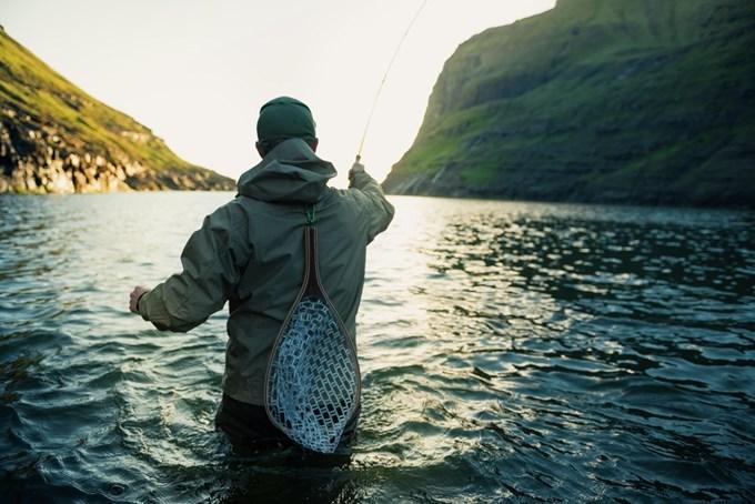 Mann som står i elv og fisker med ryggen mot kamera | foto