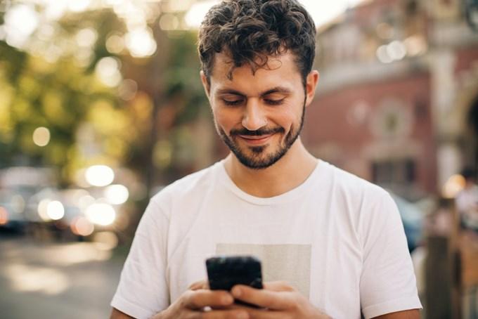 Mann smiler og ser på telefonen. Foto