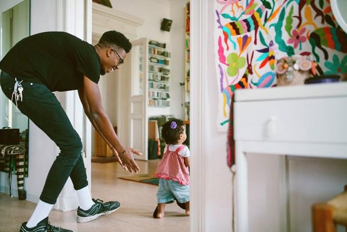 Far og datter leker i stuen. Foto
