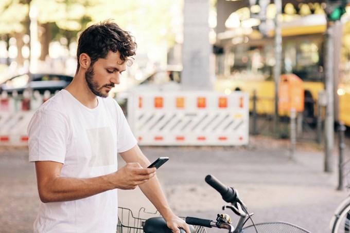Mann bruker mobilen mens han støtter seg til en sykkel. Foto
