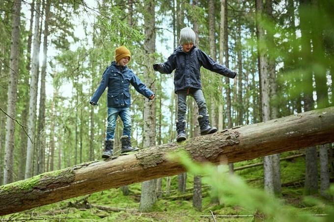 Barn balanserer på et tre som har veltet. Foto