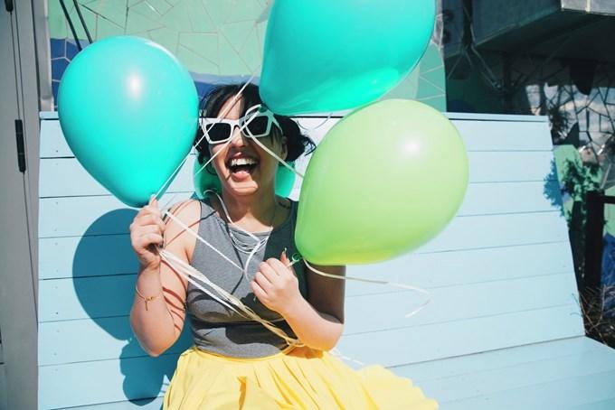Smilende kvinne holder flere ballonger. Foto.