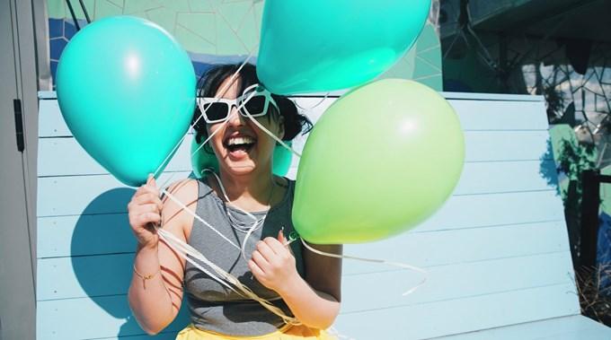 Smilende dame holder ballonger. Foto