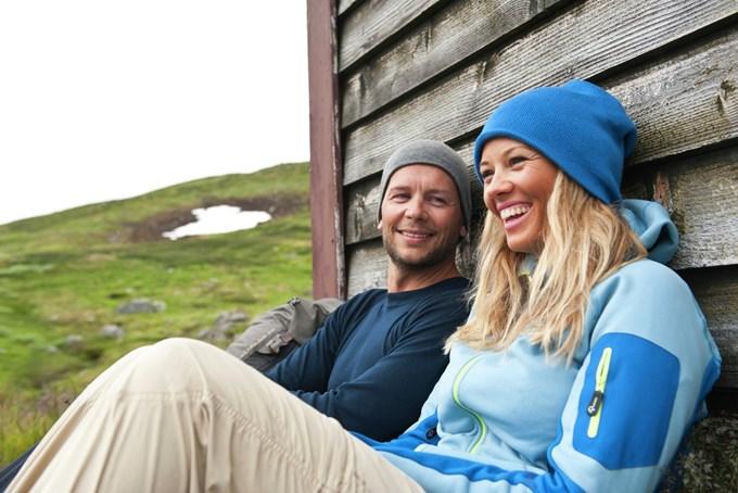Mann og dame sitter inntil hyttevegg. Foto