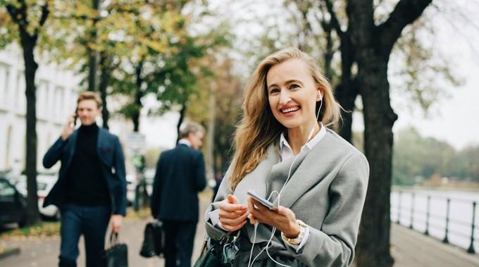 Kvinne går utendørs med mobilen i hånden.