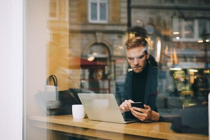 Mann sitter på cafe med laptop og mobil. Foto.