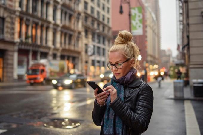 Ung kvinne på gaten trykker på telefonen. Foto