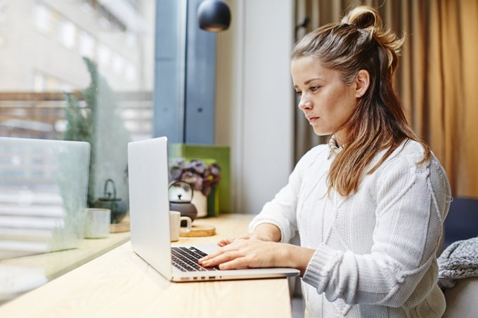 Kvinne skriver på laptop. Foto