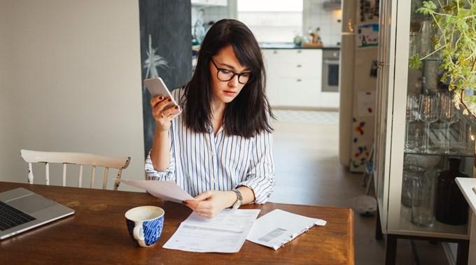 Kvinne sitter ved spisebordet med mobiltelefon i hånden og ser gjennom post. Foto