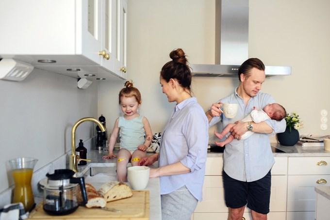 Foreldre med småbarn står på kjøkkenet | Foto